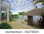 luxury mansion outside deck with Bali hut, bar and pool - stock photo