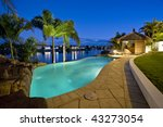 Luxurious mansion exterior at dusk overlooking pool, canal and Bali hut - stock photo