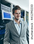 Male IT technician in front of mainframe and communication racks in data center for large organization - stock photo