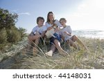 Family sitting on the beach - stock photo