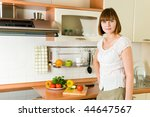 Young attractive brunette in the kitchen - stock photo