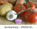 Some carrots, potatoes, onions, tomatoes, garlic and laurel on chopping board. - stock photo