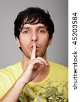 young person doing a silence gesture with his forefinger - stock photo