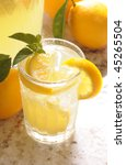 Close up of a Glass of Lemonade on counter in front of window with pitcher and lemons vertical format shallow DOF High angle - stock photo