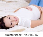 Beautiful sensuality pregnant woman lying in the bedroom - stock photo