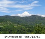 Mountain ridge, wooded slopes, small village among green trees, blue sky with white clouds                               - stock photo