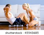 Young man performs sit ups on the floor as a young woman holds his feet. Horizontal shot. - stock photo