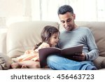 Little girl and father are enjoying reading book together - stock photo