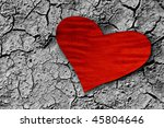 red paper heart on dry cracked ground - stock photo