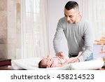 Father is changing diaper of her daughter. - stock photo