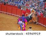 SEVILLE - APRIL 30: A bull attacks the picador during a bullfight at the Plaza de Toros de Sevilla April 30, 2009 in Seville, Spain. - stock photo