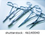 medical clamp instruments on table with shallow depth of field - stock photo