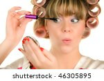 woman with hair curlers paint her eyeshadow - stock photo