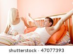 Man stretches while reclining in bed as woman sits and smiles at him. Horizontal format. - stock photo