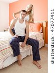 Man and woman sit on bed as woman massages man's shoulders. Vertical format. - stock photo