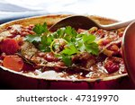 Beef stew in a red crock pot, ready to serve, garnished with parsley and lemon rind.  Traditional osso buco. - stock photo