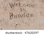 """Inscription """"Welcome to Paradise"""" on a sand. - stock photo"""
