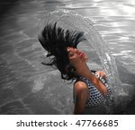 young asian lady splashing hair in a swimming pool - stock photo