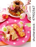 easter table with cookies decorated by child and chocolate ring cake - stock photo
