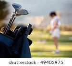 Bag of golf clubs outdoors - female player on the background - stock photo