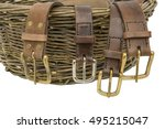 Handmade Leather Belts. Leather belts with metal buckles  arranged over a hand woven willow basket - stock photo