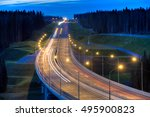 Night lighting of the highway bridge in the forest. - stock photo
