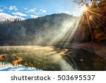 view on crystal clear lake with rocky shore and smoke on the water near the pine forest in fog at the foot of the mountain at sunrise - stock photo