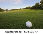 golf ball rests on bunker overlooking green of tropical florida course - stock photo