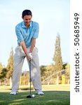 Young man playing golf leaning on the club and smiling - stock photo