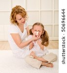 Little girl blowing nose with her mother helping - stock photo