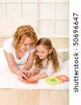 Woman and little girl playing on the floor with alphabet puzzle pieces - stock photo