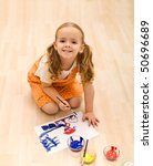 Happy girl painting sitting on the floor - top view - stock photo