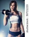 Young strong sexy woman with dumbbells. With flash effect. - stock photo