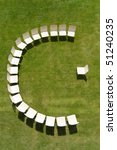 aerial perspective of some chairs arranged in a half circle on a sunny meadow. - stock photo