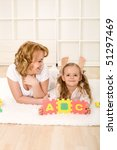 Little girl having fun learning the alphabet with her mother - stock photo