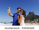 tourist couple in Rio de Janeiro taking a photo with a digital compact camera - stock photo