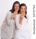 Portrait of a mother and her daughter happily eating doughnuts - stock photo