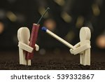 One small wooden male holds a banger and the other one holds a matchstick - stock photo