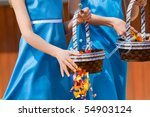 A vertical photo of two caucasian girls scattering rose petal confetti at a wedding reception - stock photo