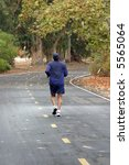 an unidentifiable person jogs on a jogging or bike trail - stock photo