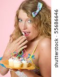 sexy model holding plate of cupcakes with twisted candles - stock photo