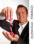 A man dropping red poker chips into his hand - stock photo