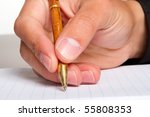 A close up of a man writing in a notebook - stock photo