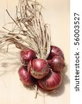 Bunch of red onions on raw wood - stock photo