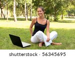 Beautiful young woman sits on a grass in a city park with the laptop. - stock photo