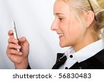A young businesswoman receiving a message on her mobile phone - stock photo