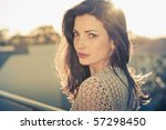 Young beautiful fashion model with hair and make-up professionally done outdoors back lit at sunset - stock photo