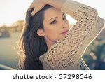 Young beautiful fashion model with hair and make-up professionally done outdoors back lit at sunset. running hands through hair. - stock photo