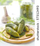 Hole fresh salted cucumber on plate with dills - stock photo