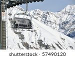 Chairlift with impressive mountains in the background - shot in Livigno, Italian Alps - stock photo